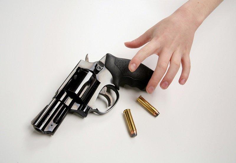 child reaching for gun
